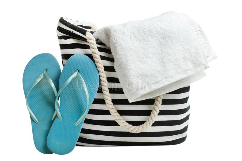 Striped beach bag with white bath towel and blue rubber slaps stock photo