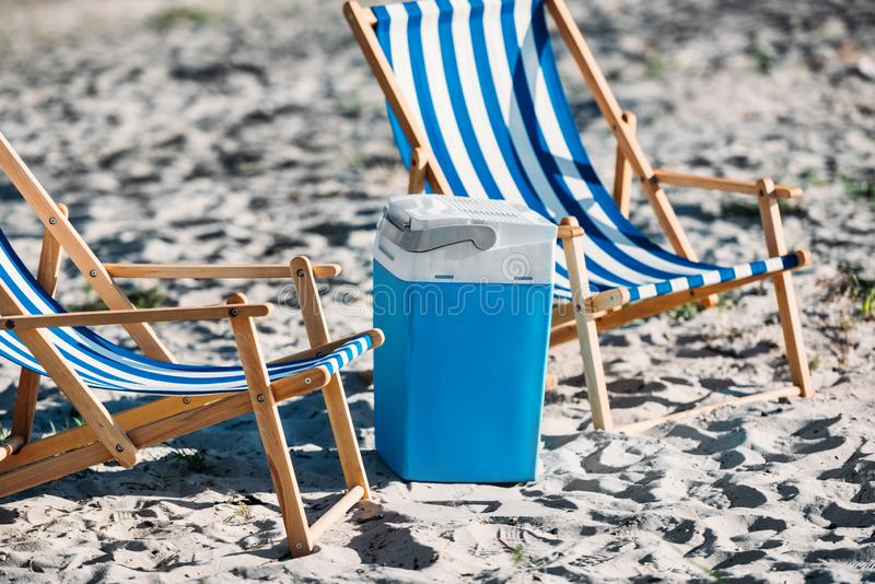 Striped beach chairs and cooler. On sand stock photography