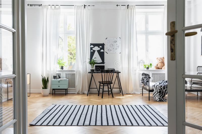 Black chair at desk in child`s room interior with windows, bed and plants. Real photo stock photo