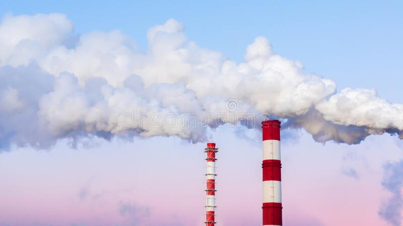 Striped chimneys emit thick white smoke in the evening blue pink sky. Air pollution, environmental problems. Tall pipes beautiful. Striped chimneys emit thick royalty free stock images