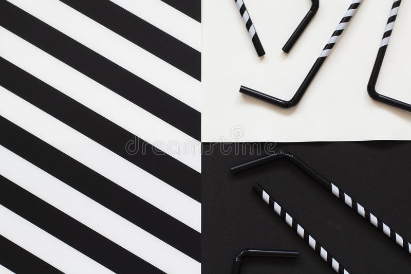 Striped cocktail straws on black and white background in minimal style. Top view, flat lay with copy space.  stock illustration