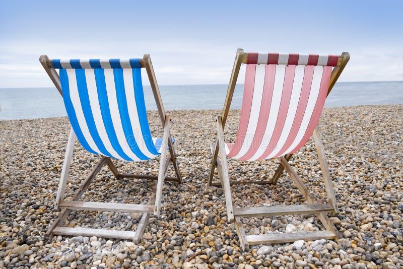 Striped deckchairs on pebble beach stock photos