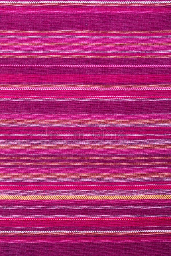 Striped fabric texture with multiple warm colors purple, purple, magenta, pink, red, maroon, orange, yellow. Close-up of the stock photos