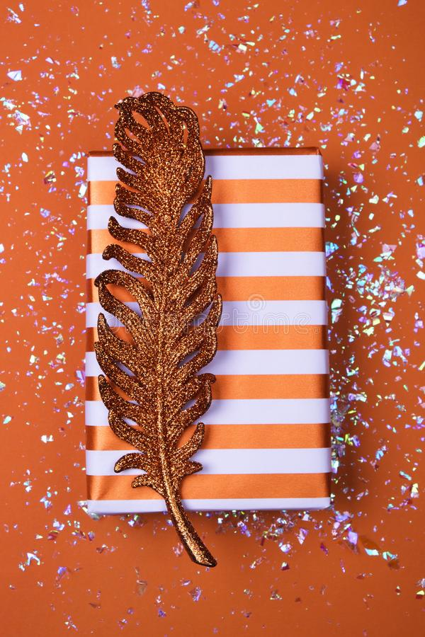 Striped gift box with a bright shiny feather. On a beautiful beige table stock image
