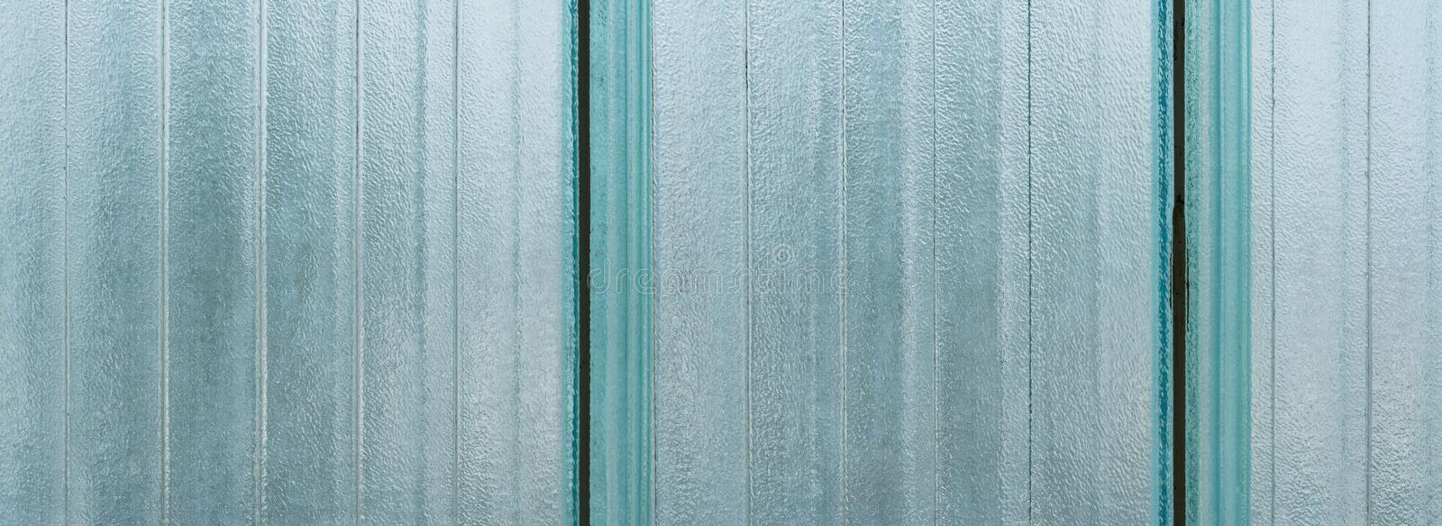 Opaque striped glass wall blocks. Architecture detail. Wide-angle background from vertical strips of big translucent bricks. Abstract blue grainy textured royalty free stock image