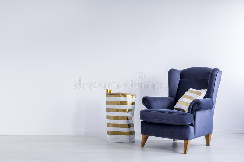 Gold pillow on blue armchair. Striped gold pillow on dark blue armchair and pattern paper bag in minimal white room stock photo