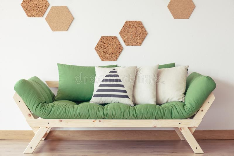 Living room with green sofa. Striped grey pillow on green wooden sofa against white wall with natural cork stock photography