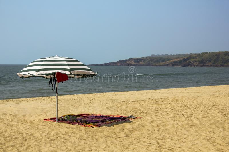 Striped large umbrella and sarong on the yellow sand of the beach against the ocean with sea waves under a clear blue sky stock photo