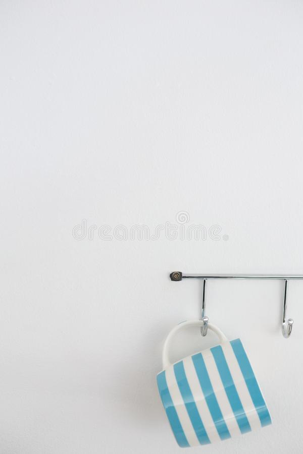 Striped mug hanging on hook. Against white wall stock photography