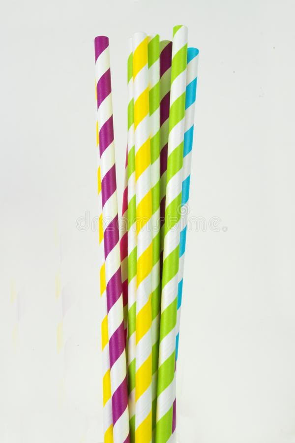 Paper straws in a vertical format on a white background. Striped, multi-colored paper straws in a vertical format against a white background stock photography