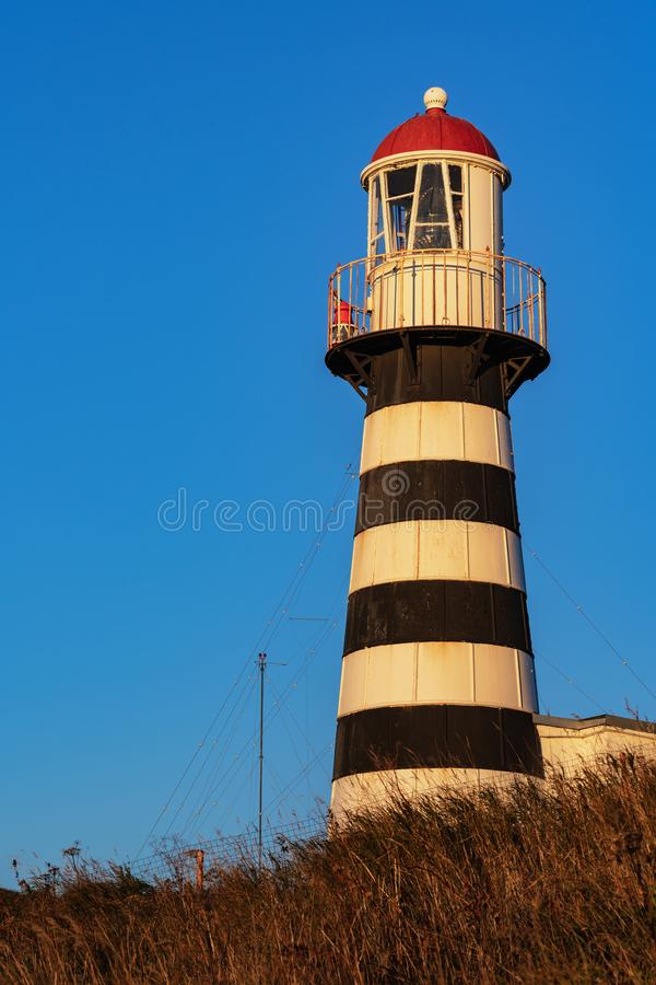 Striped old building of Petropavlovsky Lighthouse on Pacific Coast rising of sun stock photo