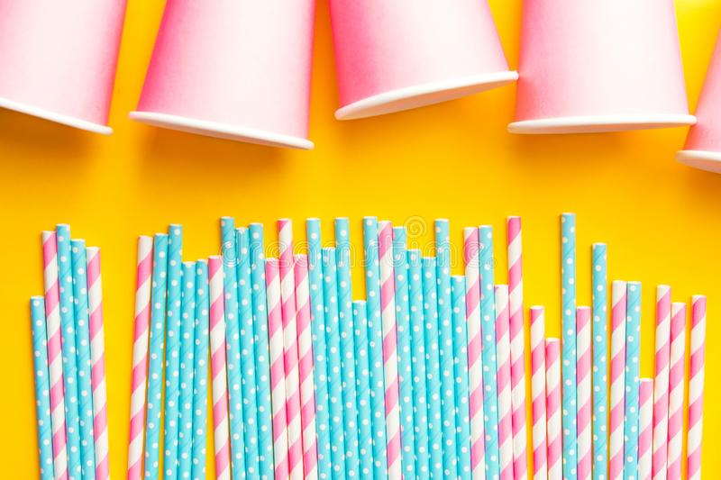 Striped pink and white blue polka dot paper drinking straws pink cups on bright yellow background. Kids birthday party celebration stock photo