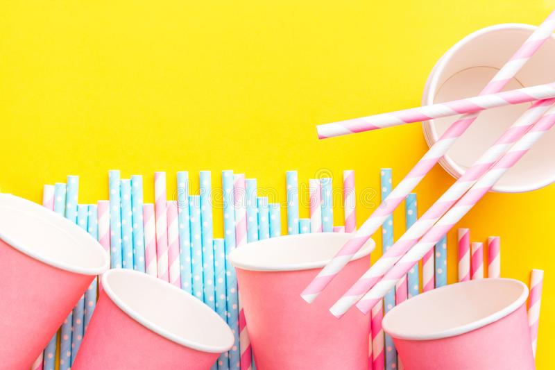 Striped pink and white blue polka dot paper drinking straws pink cups on bright yellow background. Kids birthday party celebration. Reusable eco friendly stock images