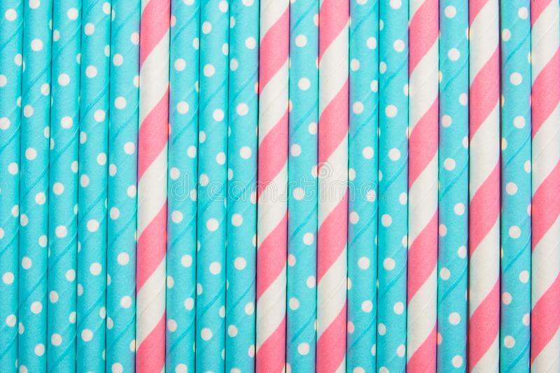 Striped pink and white blue polka dot paper drinking straws laid out as all over pattern backdrop. Kids birthday party celebration royalty free stock photos