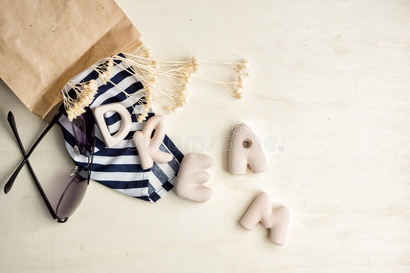 Striped scarf, sun glasses and word Dream on bright wood stock image