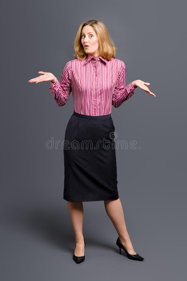 Striped shirt woman shrugging shoulders. Standing woman wearing striped shirt and shrugging her shoulders royalty free stock photography