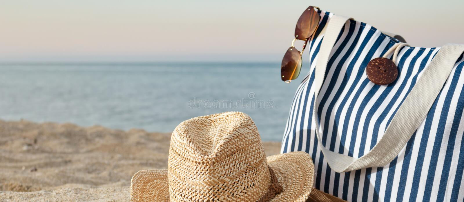 Striped summer bag with straw hat and sunglasses closeup on beach and calm sea background. Sunset time. Horisontal, copy stock photos