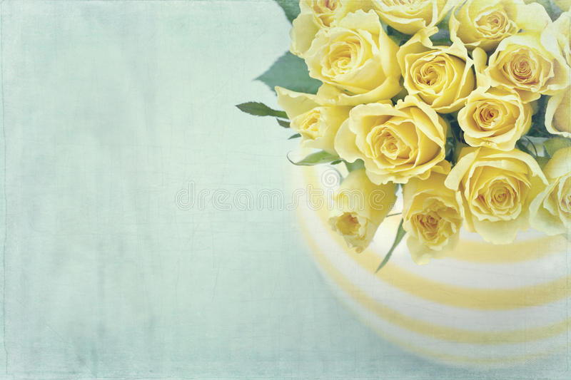 Striped vase with a bouquet of yellow roses royalty free stock image