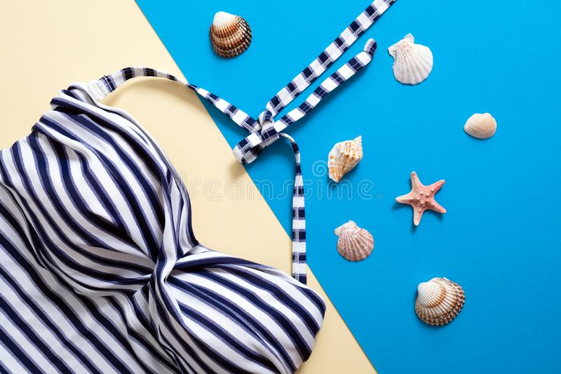 Striped women`s swimsuit and sea shells on blue and yellow background. Flat lay composition, concept of summer holidays, vacation royalty free stock images