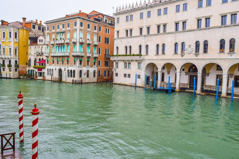 Striped and wooden mooring poles and colorful Venetian gothic architecture buildings in Venice, Italy royalty free stock photo