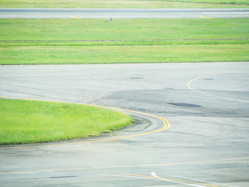 The stripes and curves of taxiway and green grass at the airport stock image