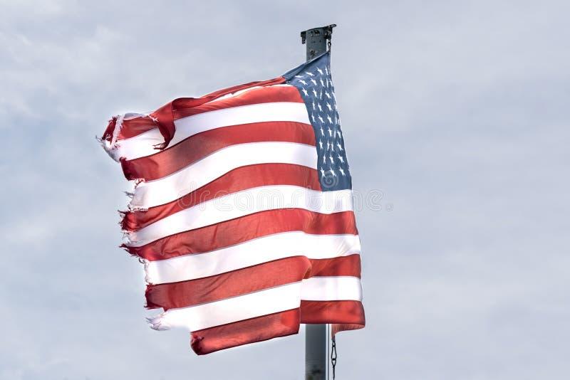 &Stripes der amerikanischen Flagge, der Sterne, zerlumptes und ausgefranst am Rand, brennend im Wind an einem grauen und düstere lizenzfreies stockbild