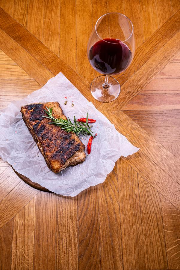 Striploin зажарило стейк говядины служило с розмариновым маслом, солью и перчинками на деревянной доске с бокалом вина r стоковая фотография