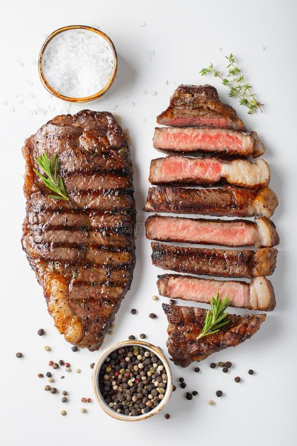 Striploin för två grillad marmorerad nötköttbiffar med kryddor som isoleras på vit bakgrund, bästa sikt arkivbilder