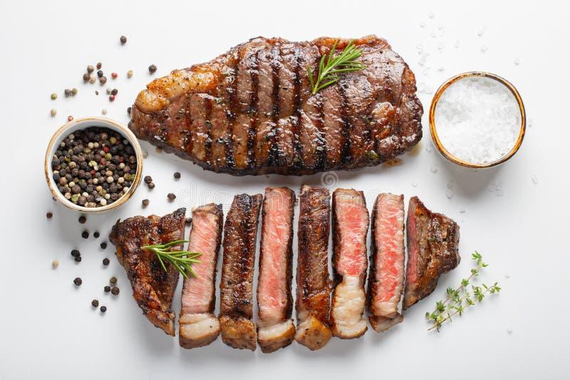 Striploin för två grillad marmorerad nötköttbiffar med kryddor som isoleras på vit bakgrund, bästa sikt royaltyfri fotografi