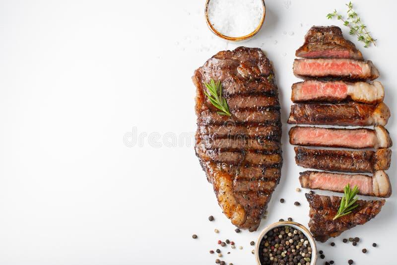 Striploin för två grillad marmorerad nötköttbiffar med kryddor som isoleras på vit bakgrund, bästa sikt med kopieringsutrymme royaltyfria foton