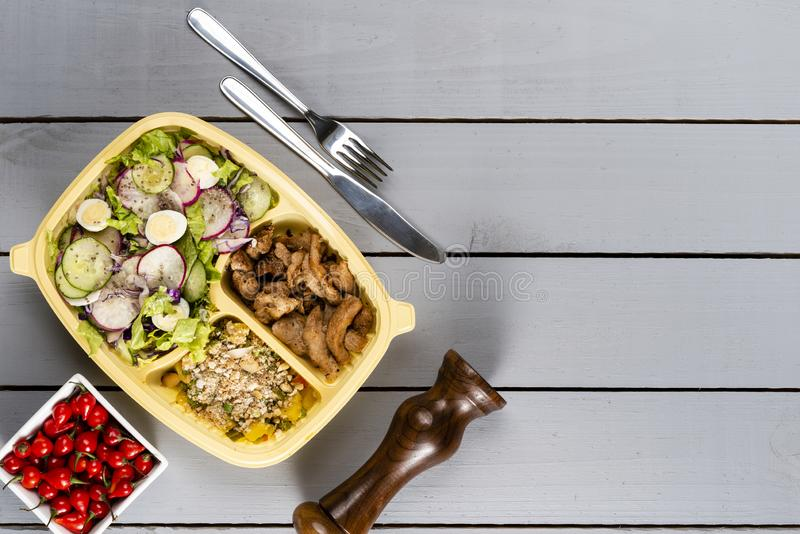 Strips of sauteed chicken and vegetables with vegetable farofa. Brazilian lunch box. Ahead meal preparation or dieting concept. to stock images