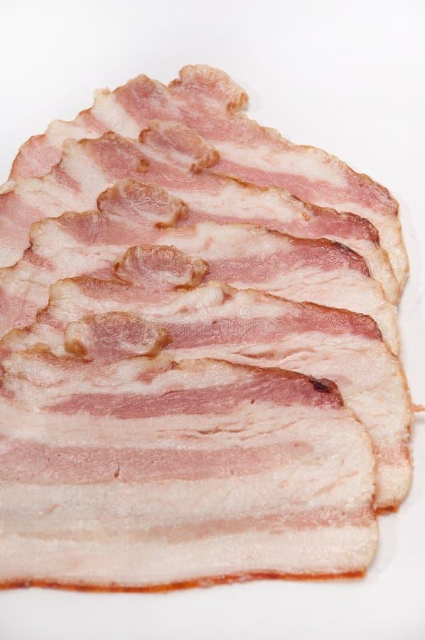 Strisce di bacon su un fondo bianco immagine stock