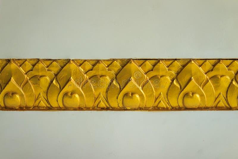Strisce dorate del loto modellate sul fondo bianco della parete Yel dell'oro fotografia stock