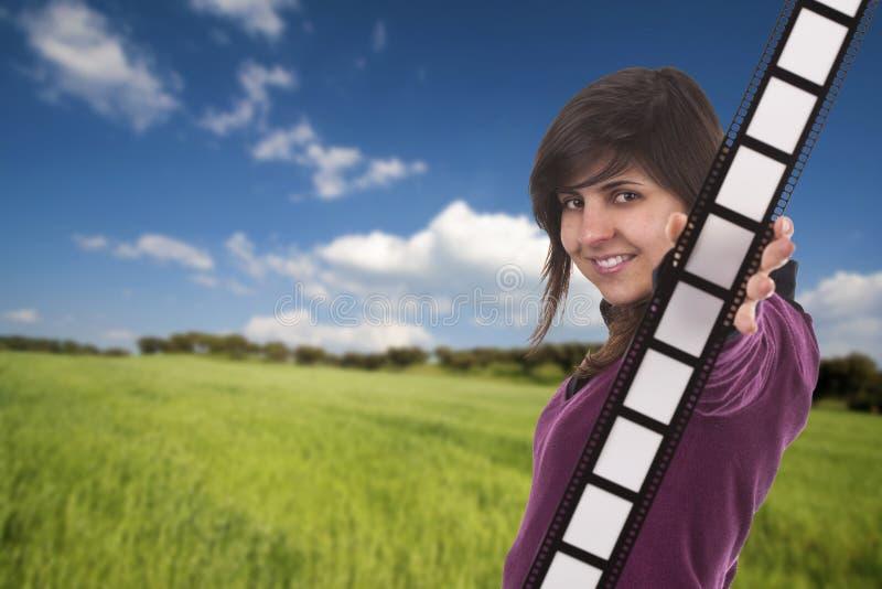 Striscia della pellicola della holding della ragazza all'aperto immagine stock libera da diritti