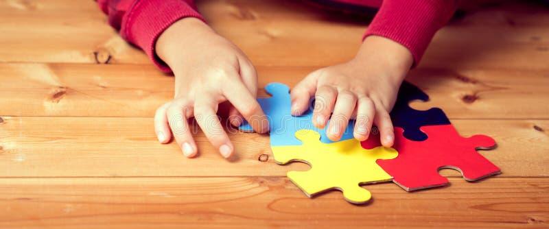 Striscione immagine delle mani di un bambino autistico che interpreta un rompicapo simbolo di consapevolezza pubblica per l'autis immagini stock libere da diritti