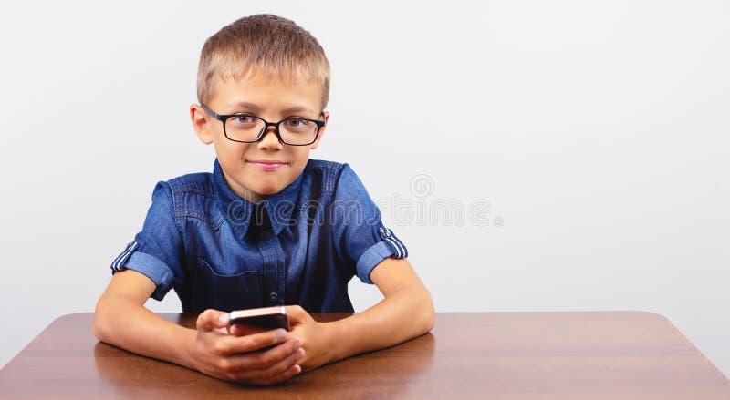 Striscione Ritratto di un ragazzo sorridente con occhiali che usa il cellulare sulla scrivania della scuola su sfondo bianco Mobi fotografia stock