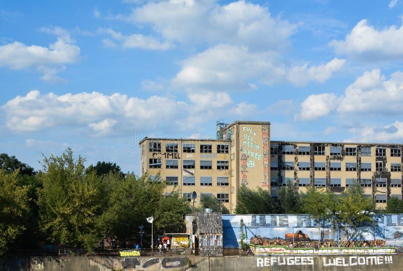 Striscioni di strada a YAAM a Berlino, Germania con edifici abbandonati immagini stock