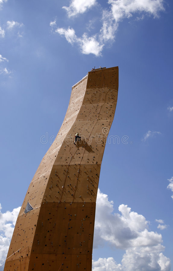 Striving for the top. Man on climbing wall working to get to the top stock image