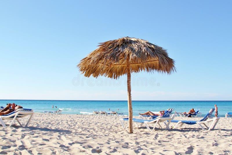 Strodak van strandparaplu op wit zandig strand stock foto's