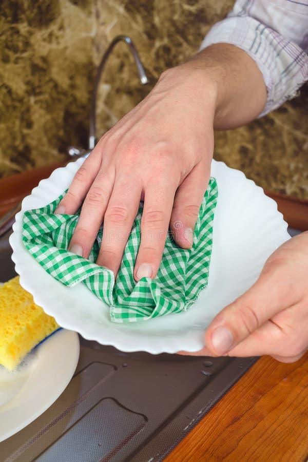 Strofinata delle mani dell'uomo con il piatto bianco pulito dell'asciugamano alla cucina fotografie stock libere da diritti
