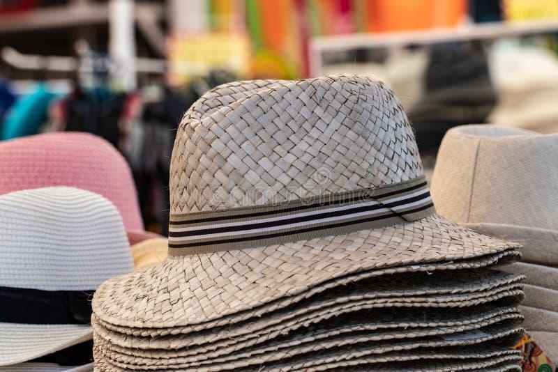 Strohhuthintergrund Nahaufnahme mit selektivem Fokus auf Strohhüten eines Stapels für Verkauf mit unscharfem Marktgeschäftshinter stockfotos