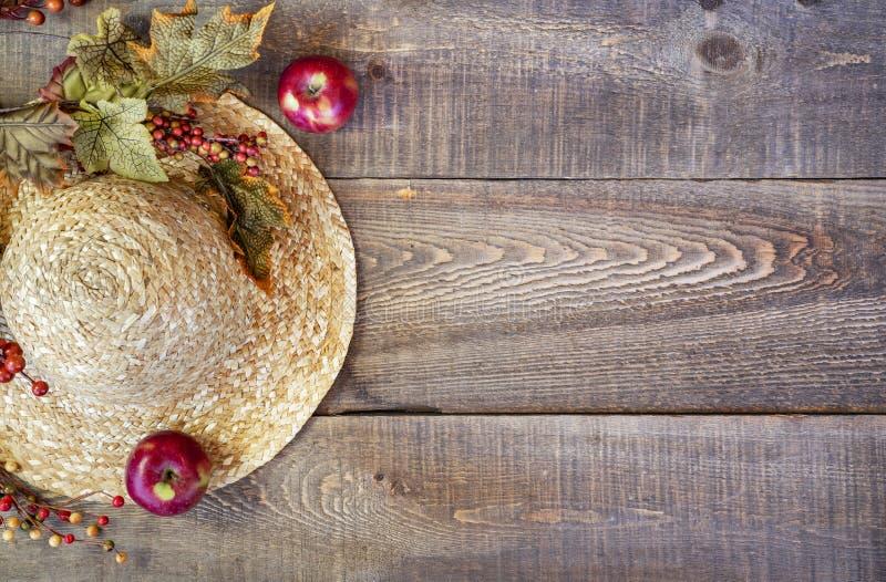 Strohoed, bladeren en de herfstbessen op rustieke houten plank backgr royalty-vrije stock foto's