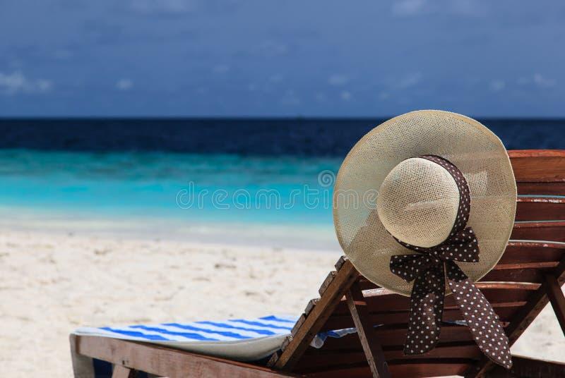 Strohoed op een zitkamerstoel bij tropisch strand stock afbeeldingen