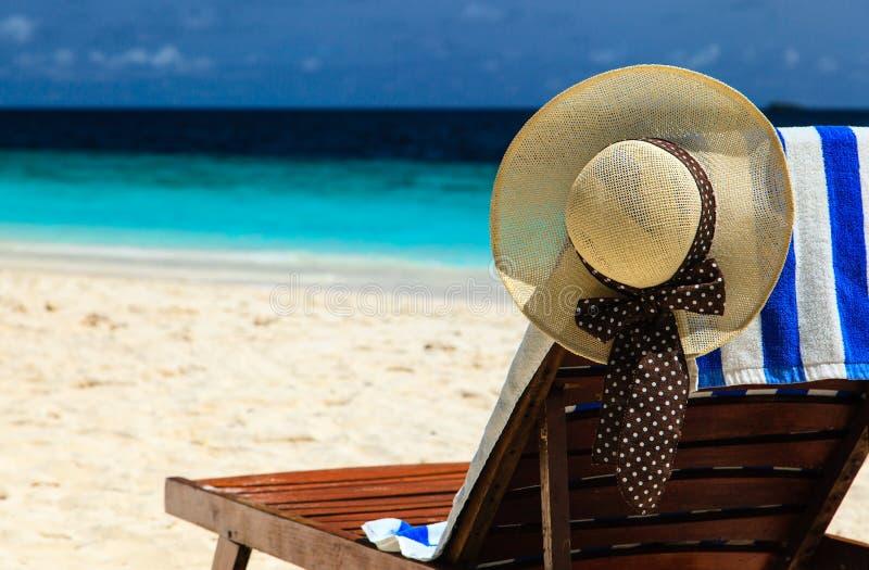 Strohoed op een zitkamerstoel bij tropisch strand stock foto's
