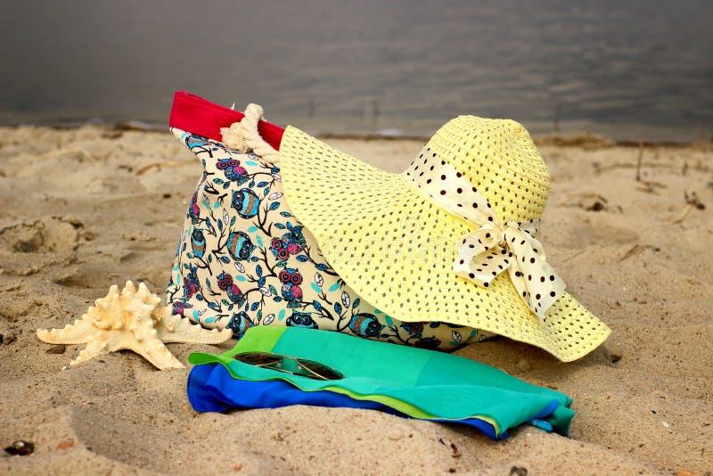 Strohoed, strandzakken die, sarongen, glazen, zeesterclose-up op de overzeese achtergrond liggen royalty-vrije stock foto