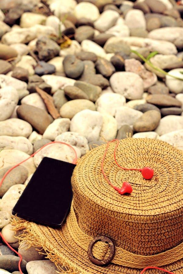 Strohoeden met smartphone, oortelefoon royalty-vrije stock foto