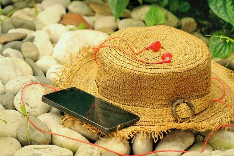 Strohoeden met smartphone, oortelefoon stock fotografie