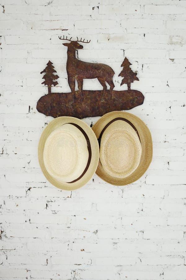 Strohoeden op een elandenhanger op witte bakstenen muur Mannelijk, vrouwelijk toebehorenconcept Skandinavische binnenlandse stijl royalty-vrije stock foto