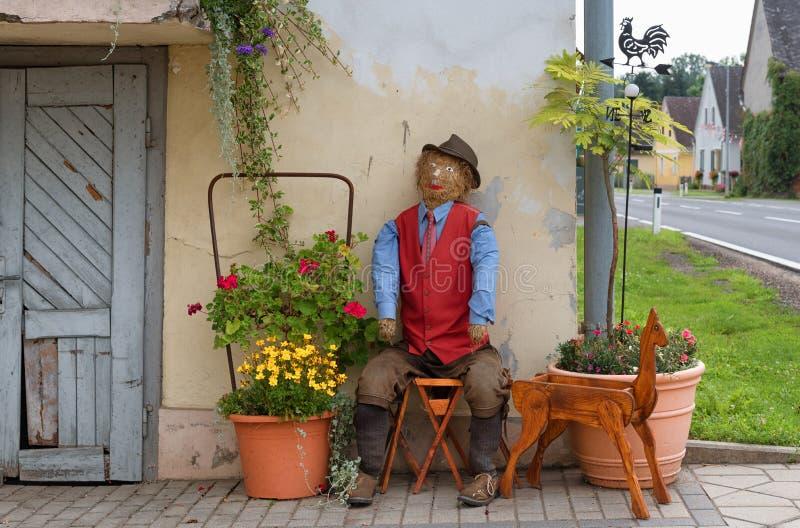 Strohpuppenlandwirt, der vor einem Bauernhaus, Erntefeier, Dekorationen in Österreich sitzt stockfotografie