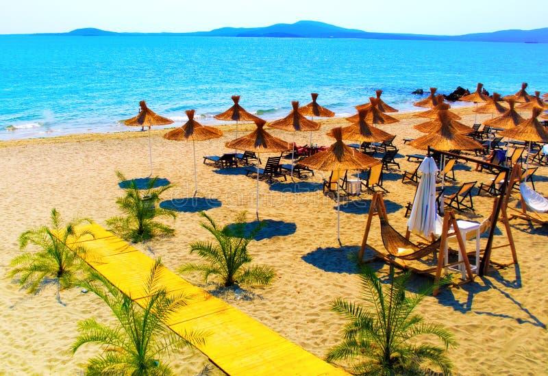 Strohregenschirme auf schönem sonnigem Strand lizenzfreies stockfoto